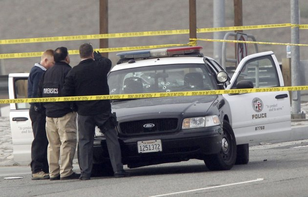 """Police investigators inspect an LAPD cruiser with bullet holes in the windshield, where a police officer was shot on Magnolia Ave. over Interstate 15 Freeway in Corona, California February 7, 2013. Authorities in California launched a statewide manhunt on Thursday for a former Los Angeles police officer who threatened """"warfare"""" on cops and was suspected in a shooting spree that has killed three and wounded two others.  REUTERS/Alex Gallardo  (UNITED STATES - Tags: CRIME LAW)"""
