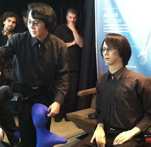"Roboticist Hiroshi Ishiguro of Osaka University (left) demos his ""Geminoid"" android lookalike (right) at the Global Futures 2045 International Congress in New York."