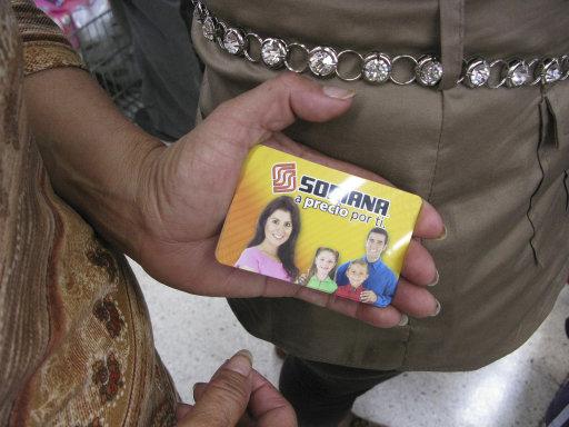 Una mujer muestra una tarjeta prepagada de regalo mientras hace fila en un supermercado Soriana en la ciudad de México, el martes 3 de julio de 2012. Muchas de las personas en el supermercado dijeron que fueron a canjear las tarjetas, que dijeron haber recibido del partido que ganó la presidencia de México, alimentando las acusaciones de que las elecciones del domingo estuvieron manchadas por una enorme compra de votos. (Foto AP/Marco Ugarte)