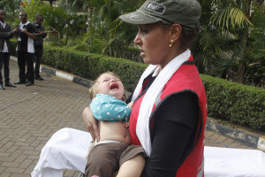 A Red Cross assistant helps a child outside the Westgate…