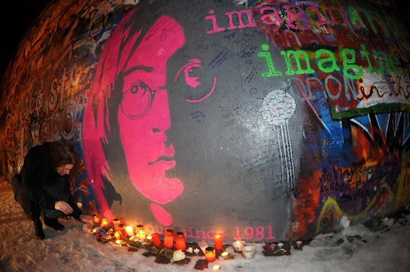 A young woman lights a candle in front of  John Lennon's wall memorial to commemorate the 30th anniversary of the musician's death on December 8, 2010 in Prague