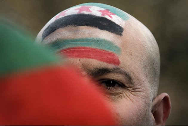 An unidentified protestor seen behind a Bulgarian flag has his face painted with Bulgarian and the Syrian revolutionary flag as he attends protest against the regime of Syrian President Bashar al-Assa