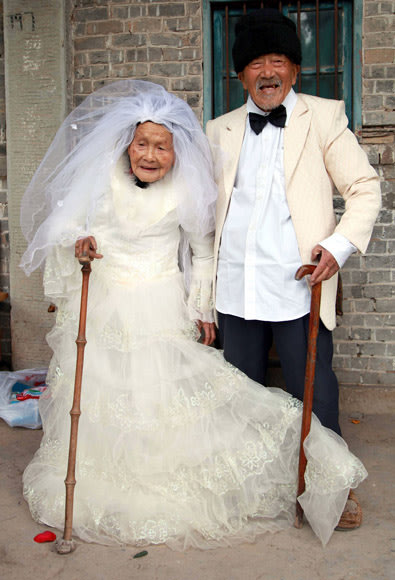 Wu Conghan, 101 years old, and his 103-year-old wife pose for photos while wearing wedding clothes at their home in a village of Nanchong