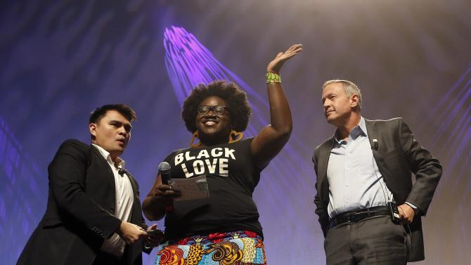 As dozens protesters shout, Tia Oso of the National Coordinator for Black Immigration Network, center, walks up on stage interrupting Democratic presidential candidate, former Maryland Gov. Martin O'Malley, right, as moderator Jose Vargas watches at left, during the Netroots Nation town hall meeting, Saturday, July 18, 2015, in Phoenix. (AP Photo/Ross D. Franklin)