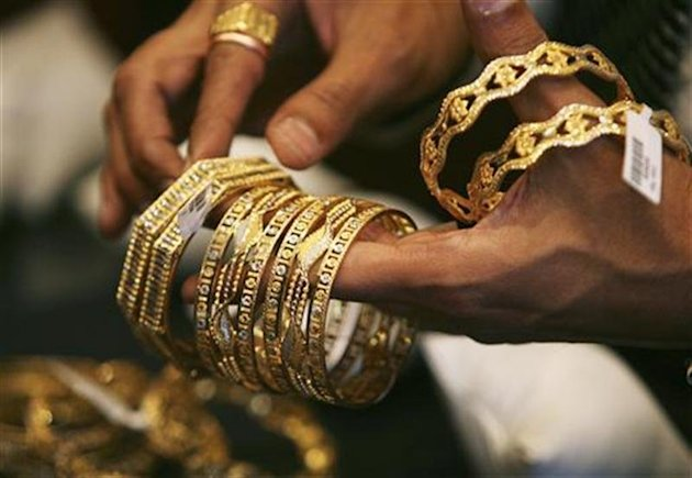 A shopkeeper shows gold bangles to a customer at a jewellery shop in Mumbai