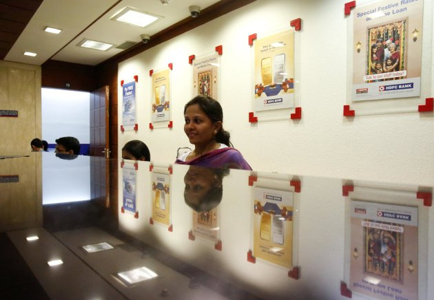 A teller waits for customers at a counter in a HDFC Bank branch in Mumbai