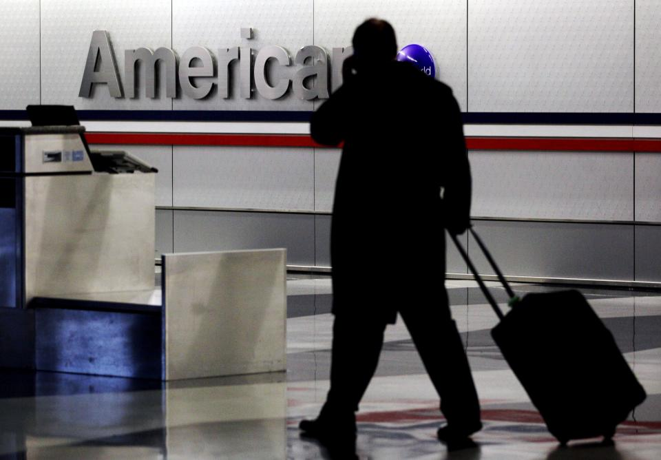 FILE - In this Tuesday, Nov. 29, 2011, file photo, a passenger walks through an American Airlines baggage claim area at O'Hare International Airport...
