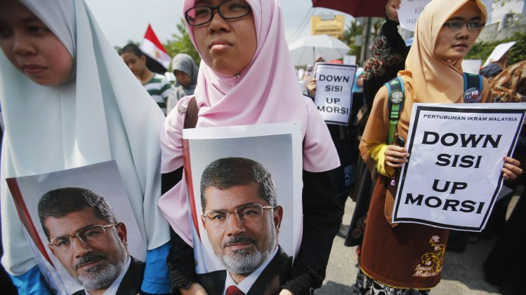 Supporters of Egypt's ousted President Mursi hold his pictures during demonstration outside Egyptian embassy in Kuala Lumpur