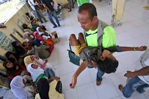 An aid worker carries a sick Rohingya boy at a temporary…