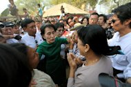 Myanmar opposition leader Aung San Suu Kyi talks with crying villagers during a visit to Tone village, an area near the Letpadaung copper mine project, in Monywa, 760 kilometers (450 miles) north of Yangon, central Myanmar, Thursday, March 14, 2013. Suu Kyi met with rare public scorn while trying to justify an official report endorsing continued operation of the copper mine in northwestern Myanmar opposed by many local residents. (AP Photo/Khin Maung Win)