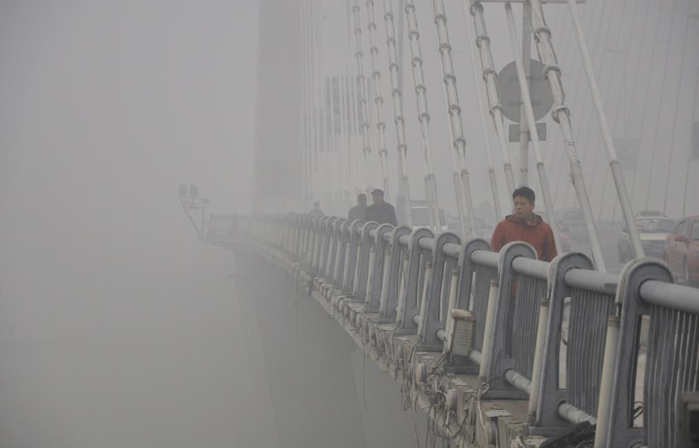 People walk on a bridge during a smoggy day in Jilin