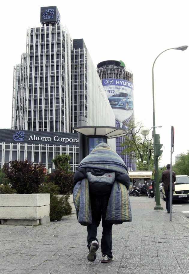 Homeless man walks at the financial district in Madrid