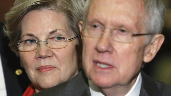 U.S. Senator Warren stands behind Senate Majority Leader Reid after leadership elections for the Congress in Washington