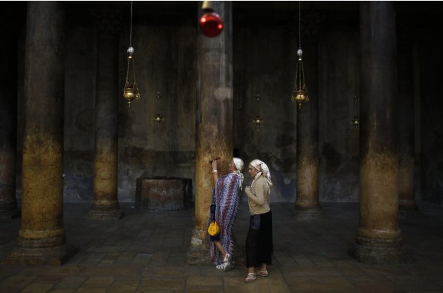 A tourist takes a photograph in the Church of the Nativity, in Bethlehem
