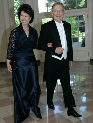 FILE - In this May 7, 2007 file photo, Secretary of Labor Elaine Chao, left, and Senate Minority Leader Mitch McConnell, R-Ky., walk through the Booksellers Area as they arrive for the State Dinner in honor of Queen Elizabeth II and her husband Prince Philip at the White House in Washington. McConnell is expected to defend his wife, Elaine Chao, in the face of some tweets he didn't much care for. The group The Progress Kentucky said McConnell's wife, former U.S. Labor Secretary Elaine Chao who was born in Taiwan, may be the reason why U.S. jobs are going to China. The group later removed the tweets and apologized. (AP Photo/Haraz N. Ghanbari)