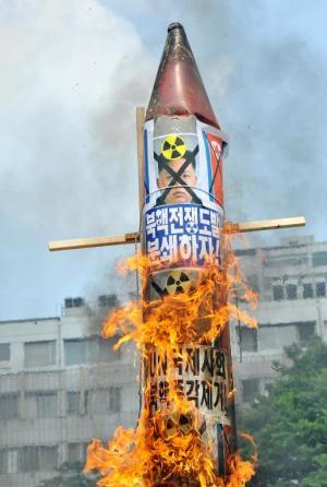 South Korean conservative activists burn a mock missile…