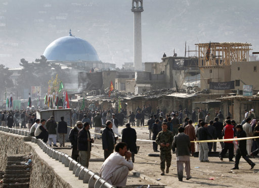 Afghans are seen near the scene of a suicide attack in Kabul, Afghanistan, Tuesday, Dec. 6, 2011. A suicide bomber struck a crowd of Shiite worshippers marking a holy day Tuesday in the Afghan capital killing scores of people in an unprecedented wave of violence against the minority Islamic sect in Afghanistan. (AP Photo/Musadeq Sadeq)