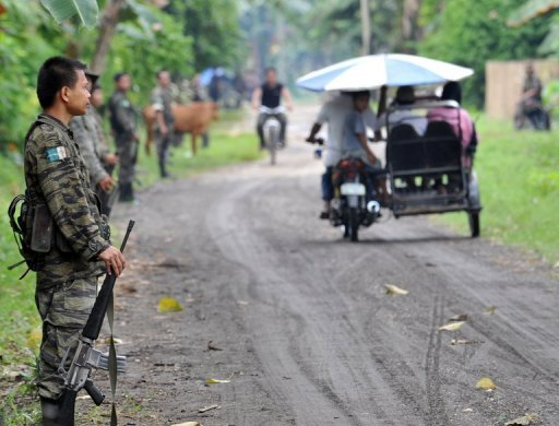<p>This file photo shows members of the southern Philippine rebel group, the Moro Islamic Liberation Front (MILF), lining a street as villagers pass by, in a town on Mindanao island, on September 19, 2009. The United States has warned Americans against travel to the southern Philippines just days after Australia and Canada issued similar advice.</p>