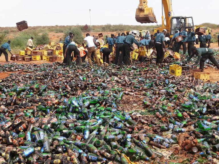 Sharia enforcers destroy thousands of bottles of beer outside northern Nigeria's largest city of Kano on November 27, 2013