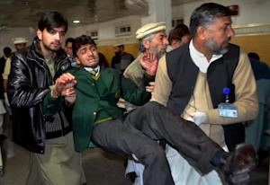 Pakistani volunteers carry a student injured in the …