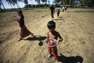 People displaced by recent violence in Pauktaw carry meat that is distributed as aid at an Owntaw refugee camp for Muslims outside Sittwe October 31, 2012. REUTERS/Soe Zeya Tun