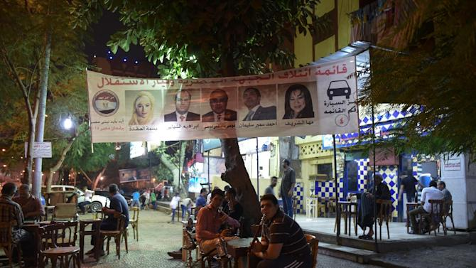 Egyptians smoke water-pipes under a banner bearing portraits of candidates for the upcoming parliamentary elections in the Giza district of the capital, Cairo, on October 14, 2015