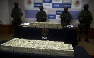 "Mexican army soldiers stand by the more than $15 mn in cash that was seized on November 18 during the regional ""Operation Fox"" in Tijuana. (AFP Photo/Yuri Cortez)"