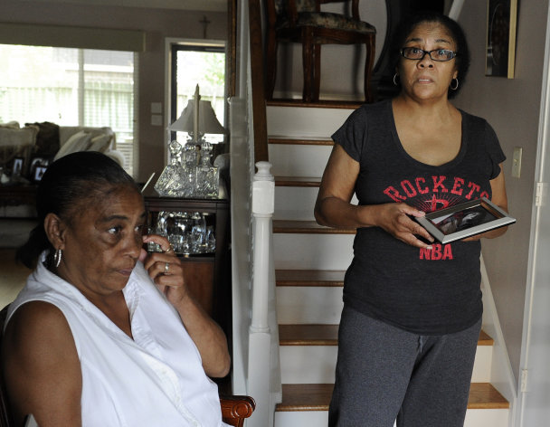 Bevenley Thomas, right, talks about niece Army Spc. Brandy Fonteneaux shown in a family snapshot as she stands beside her sister and Brandy's mother Verona Fonteneaux Saturday, Dec. 1, 2012, in Houston. Sgt. Vincinte Jackson is charged with murder and premeditated murder in Spc. Fonteneaux's death. (AP Photo/Pat Sullivan)