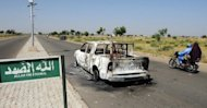 The wreckage of burnt police patrol pick-up truck abandoned on the side of a road in Damaturu in 2011. Gunfire and explosions rocked the northeastern Nigerian city of Damaturu on Saturday as security forces launched a pre-emptive offensive against Boko Haram Islamists. (AFP Photo/Pius Utomi Ekpei)
