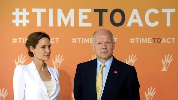 Britain's Foreign Secretary William Hague and US actress and campaigner Angelina Jolie pose for pictures upon arrival to co-host the four-day Global Summit to End Sexual Violence in Conflict in east London on June 10, 2014