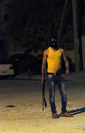 A masked Libyan gunman stands on a street in Benghazi, …