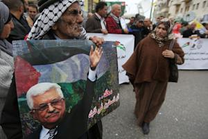 Palestinian supporters of the Fatah movement hold placards …