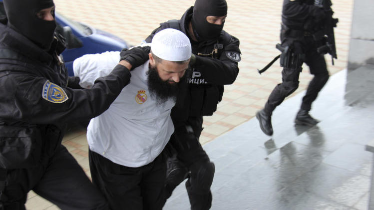 Bosnian police officers hold a suspected man who was detained during an action in the Bosnian capital of Sarajevo, on Wednesday, Sept. 3, 2014. Bosnian police say they have detained 15 people suspected of having fought in Syria and Iraq or of recruiting and funding other Balkan men to join the Islamic militants there. (AP Photo/Amel Emric)