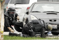 Los Angeles Police bomb squad members check for explosive devices outside a Bank of America branch in Los Angeles Wednesday, Sept. 5, 2012. Authorities say two gunmen kidnapped a bank manager, held her overnight and strapped a device to her stomach before robbing a Bank of America. The woman was told by the robbers the device was an explosive. The woman then had employees take money from the bank and put it outside. The suspects remain at large (AP Photo/Damian Dovarganes)