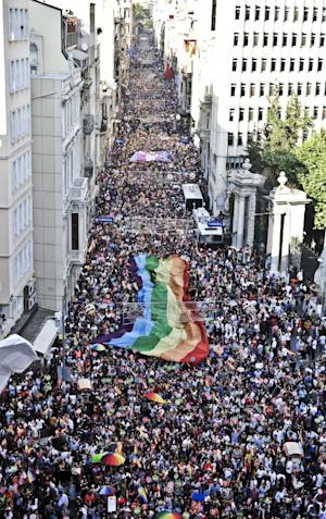People hold a giant rainbow flag during a gay pride …