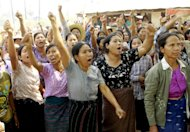 Villagers shout slogans during a protest against a recent report of a commission which investigated the Letpadaung mine's operations and a police crackdown last November that badly injured scores of protesters, during a visit by Myanmar opposition leader Aung San Suu Kyi in Tone village, an area near the mine in Monywa, 760 kilometers (450 miles) north of Yangon, central Myanmar, Thursday, March 14, 2013. Suu Kyi met with rare public scorn while trying to justify the official report endorsing continued operation of the copper mine in northwestern Myanmar opposed by many local residents. The report, made public Tuesday, said honoring the mining contract with a Chinese joint venture outweighed villagers' demands that mining operations be halted because of alleged social and environmental problems. It only mildly criticized police, despite the injuries caused to protesters, mostly Buddhist monks, by the use of incendiary smoke bombs. (AP Photo/Khin Maung Win)