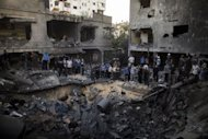 "Palestinians gather around a crater caused by an Israeli air strike on the al-Dallu family's home in Gaza City. China has called for ""maximum restraint"" by all parties, especially Israel, in the Gaza Strip conflict as the death toll from air strikes on the territory rose to 87"