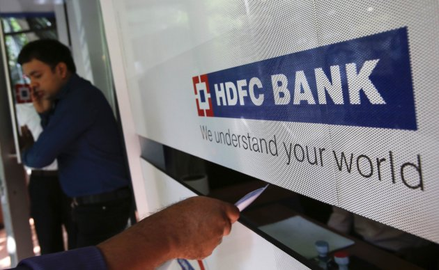A customer walks out of a HDFC Bank branch as another deposits a cheque at a counter in Mumbai