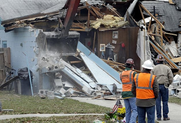 Demolition experts watch as the home of Jeff Bush, 37, is destroyed Sunday, March 3, 2013, in Seffner, Fla. The 20-foot-wide opening of the sinkhole was almost covered by the house, and rescuers said there were no signs of life since the hole opened Thursday night. (AP Photo/Chris O'Meara)