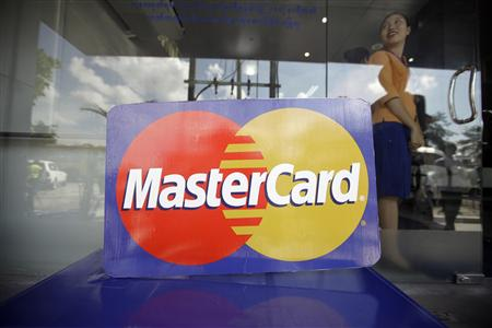 An employee stands behind a MasterCard logo during the launch of the international credit card issuer's first ATM transaction in Myanmar, in Yangon, in this November 15, 2012 file photo. Two banks owned by tycoons associated with Myanmar's former military regime will start to do business with U.S. companies and investors in the latest reward for the Southeast Asian country's rapid political transformation. The U.S. Treasury Department said on February 22, 2013, it would issue a general licence for four of Myanmar's biggest banks - Myanma Economic Bank, Myanma Investment and Commercial Bank, Asia Green Development Bank and Ayeyarwady Bank - allowing U.S companies and citizens to deal with them. REUTERS/Soe Zeya Tun/Files