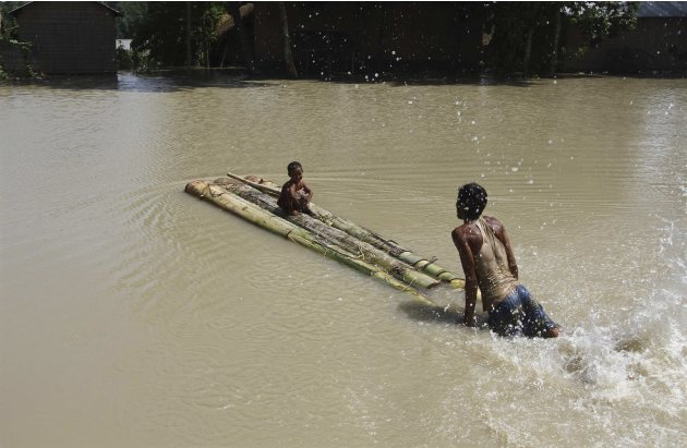 A flood-affected man pushes a temporary raft carrying his son through the flood waters after heavy rains at Mayang village