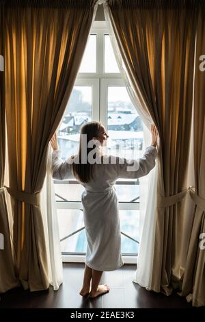 woman in bathrobe opening bedroom