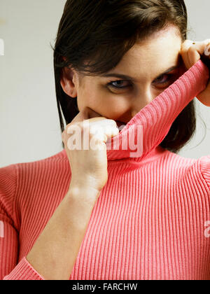 woman hiding her face with black polo neck jumper wearing ...