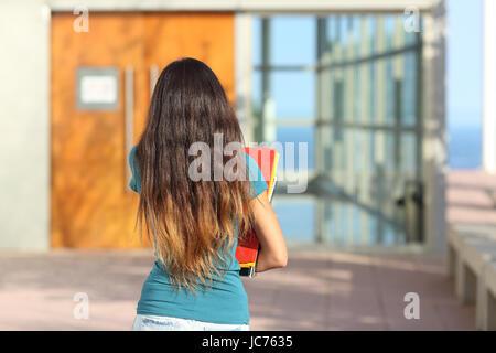 A Young Woman Walking Towards A Door Wearing A Long White