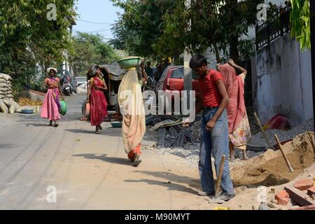 Indian women working on a building site, carrying sand and ...