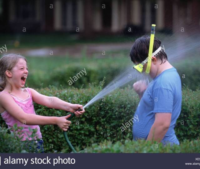A Young Girl Squirts Water At Her Brother With A Garden Hose
