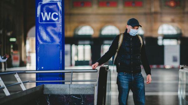 Hombre con cubrebocas bajando escaleras electricas durante pandemia