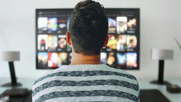 una persona mirando su televisión con muchas opciones de películas