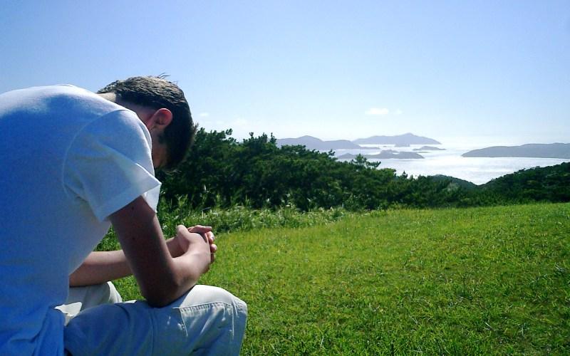 Homme priant devant la pureté d'un paysage