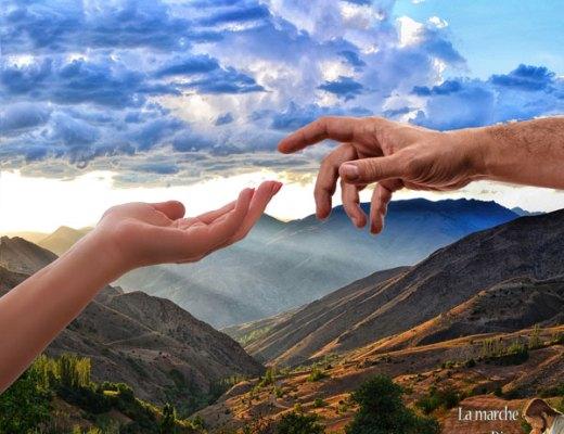 Mains qui se touchent sur fond de montagnes éclairées par dieu